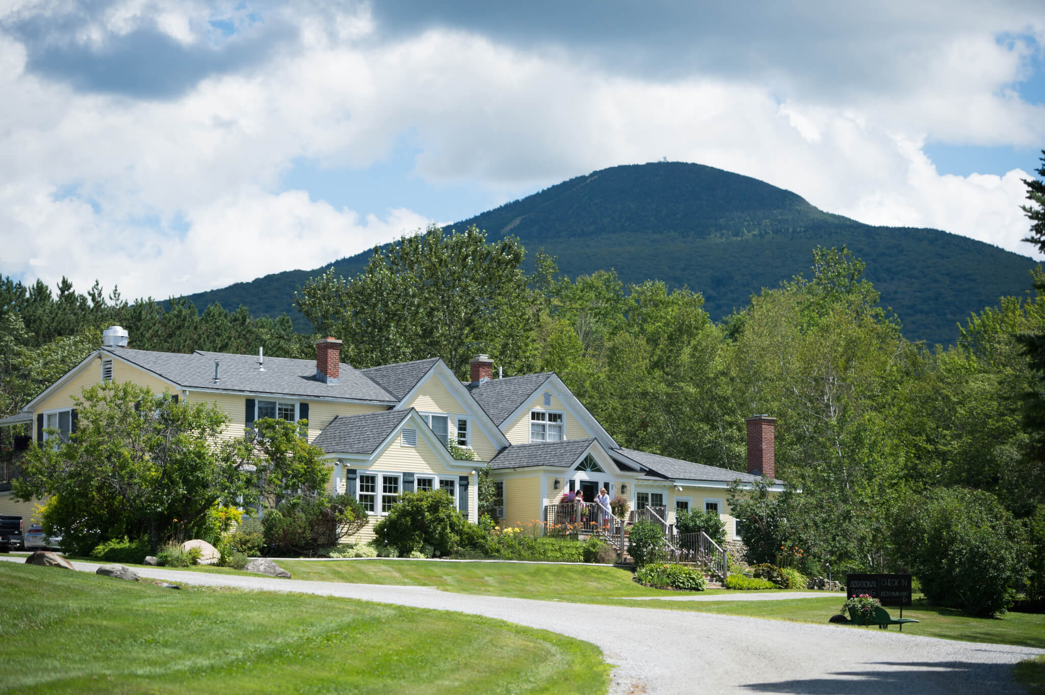 Red Clover Inn exterior with guests on the deck. Pick Mountain is behind the inn.
