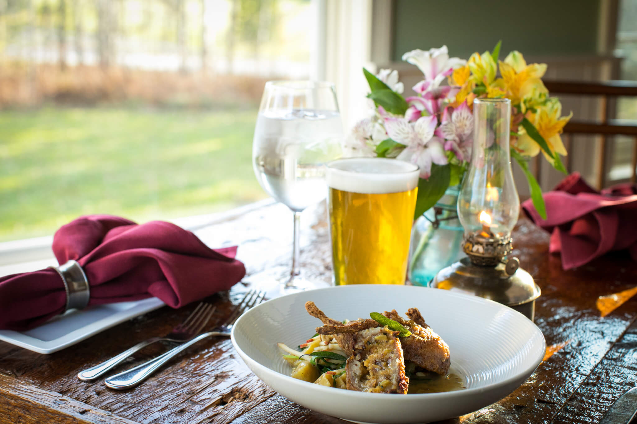 Plated Red Clover Restaurant meal with local beer and flowers. Window overlooking the lawn behind dinning room table.