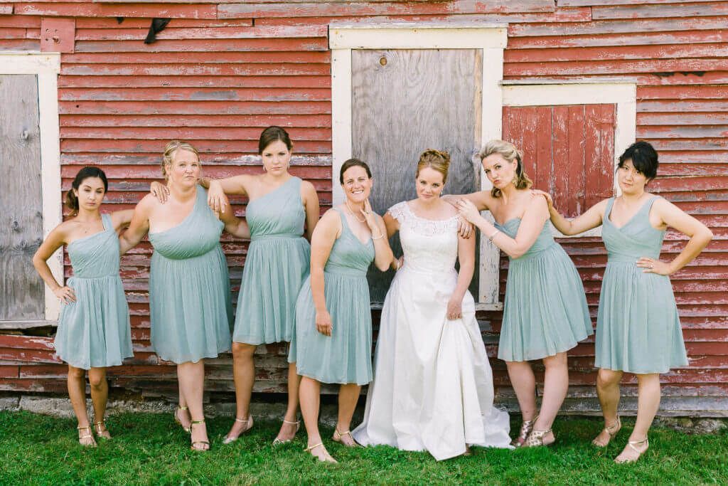 Bride and Bridal Party near Red Clover barn. Bridesmaids wearing blue dresses and heels.