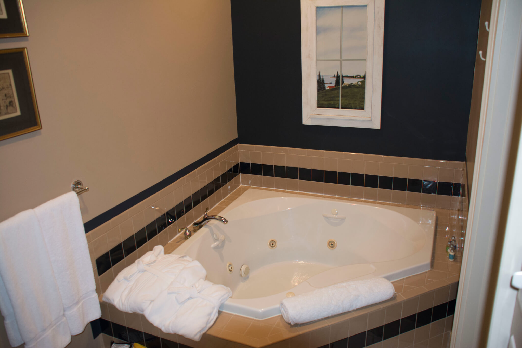 Jetted tub in the corner of the room with towels and bathrobes