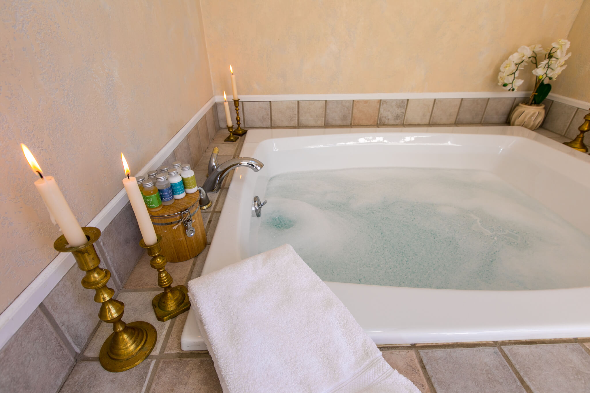 Bubble bath with lit candles and artisan soaps. Towel on the side of tiled tub.