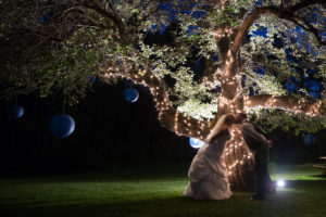 Bride and groom outdoors at night. Lights and paper lanterns on apple tree