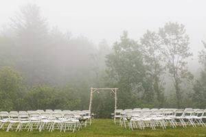 White chairs setup in front of birchwood archway. Foggy trees in the background.