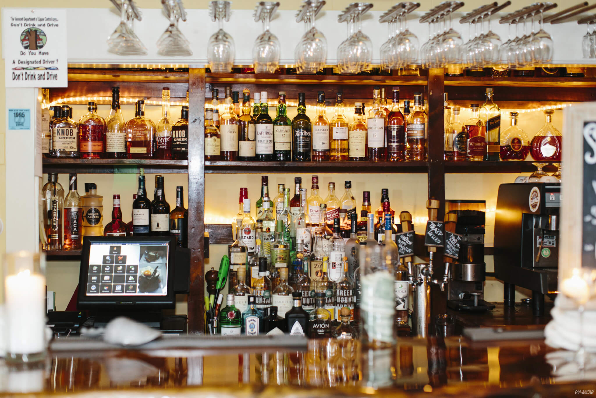 Bottles of liquor and mixers at the Red Clover Tavern Bar. Clean glasses hang above the bar.