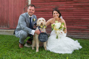 Bride and groom with dog in front of red barn.