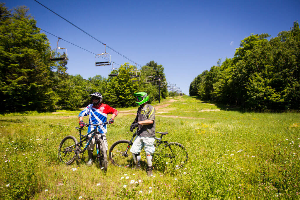 Two bikers on Killington in summer. Flowers and grass in foreground, with chair lifts and trees in the background