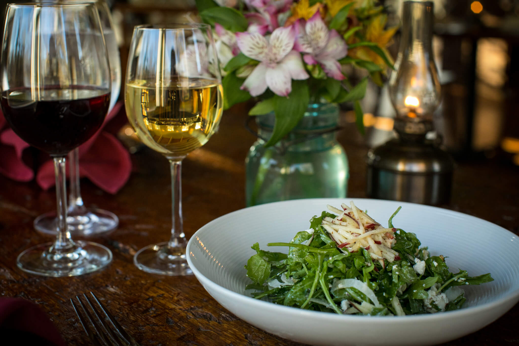 Red Clover signature salad with two glasses of wine on a set table