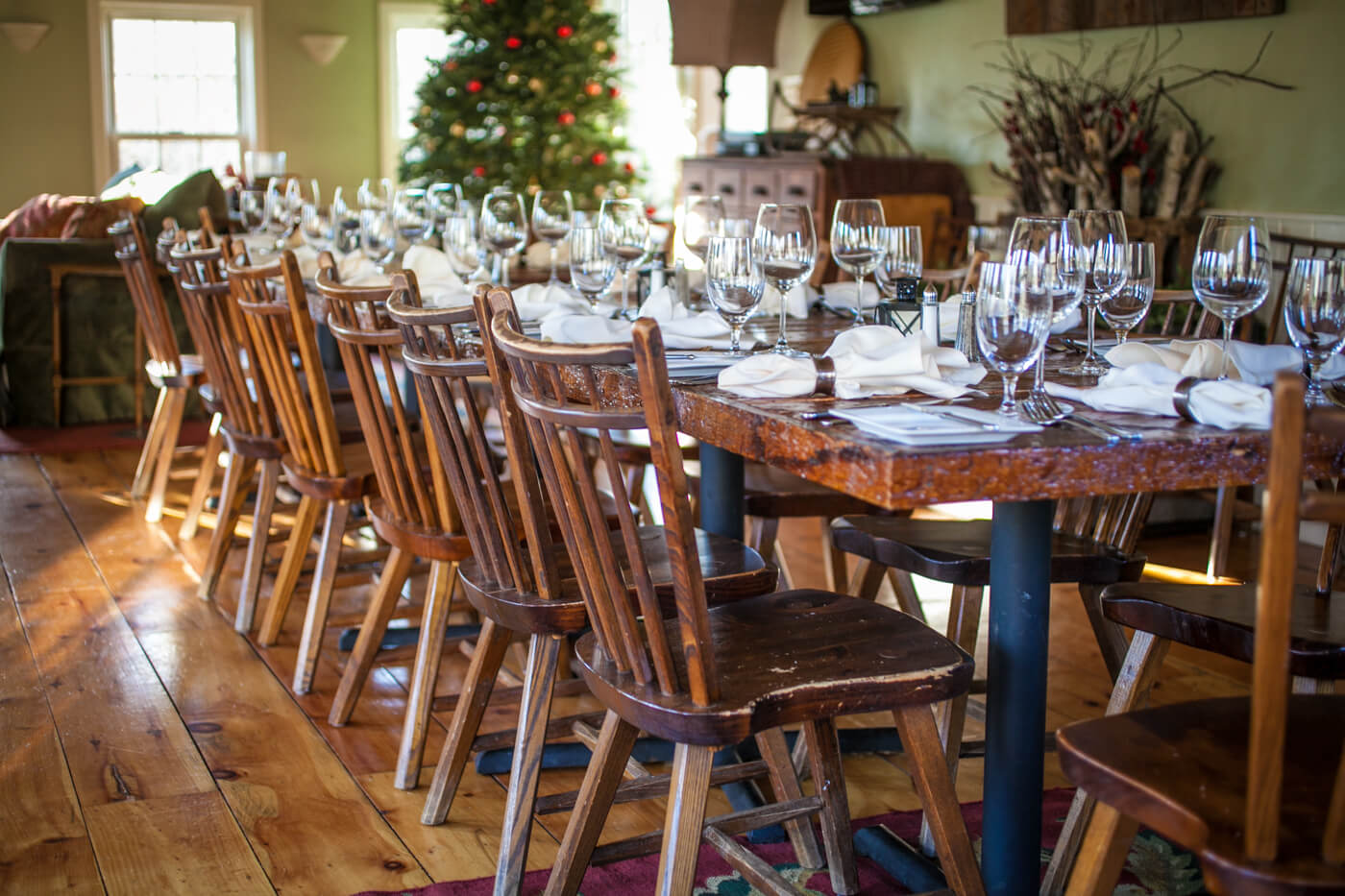 Banquet tables with wine dinner settings. Decorated Christmas tree in the background.
