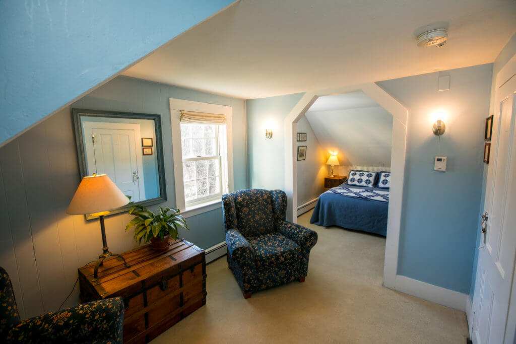 Queen-sized bed within sleeping alcove, comfortable seating and chest with lamp.