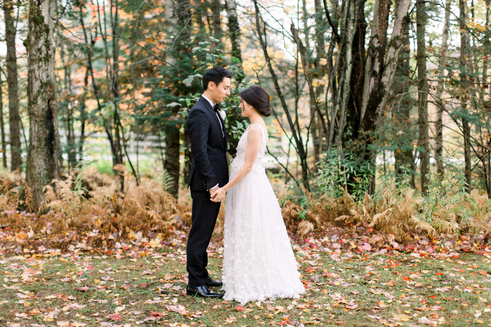 bride and groom outdoors in fall. leaves and greenery in background.