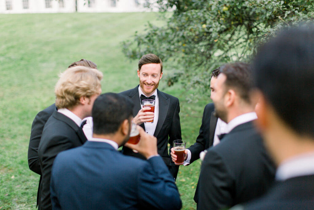 Groom and groomsmen sharing a beer on the Red Clover lawn.
