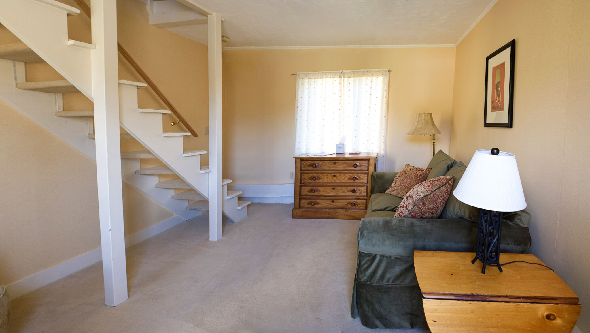 Couch with dresser and lamp