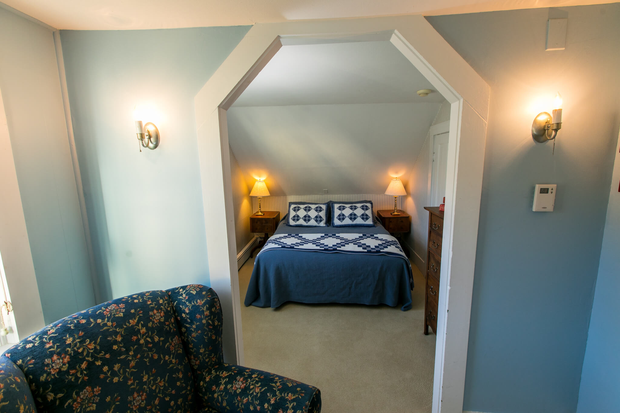 Sleeping alcove with two bedside tables and lamps. Dresser and closet next to bed.
