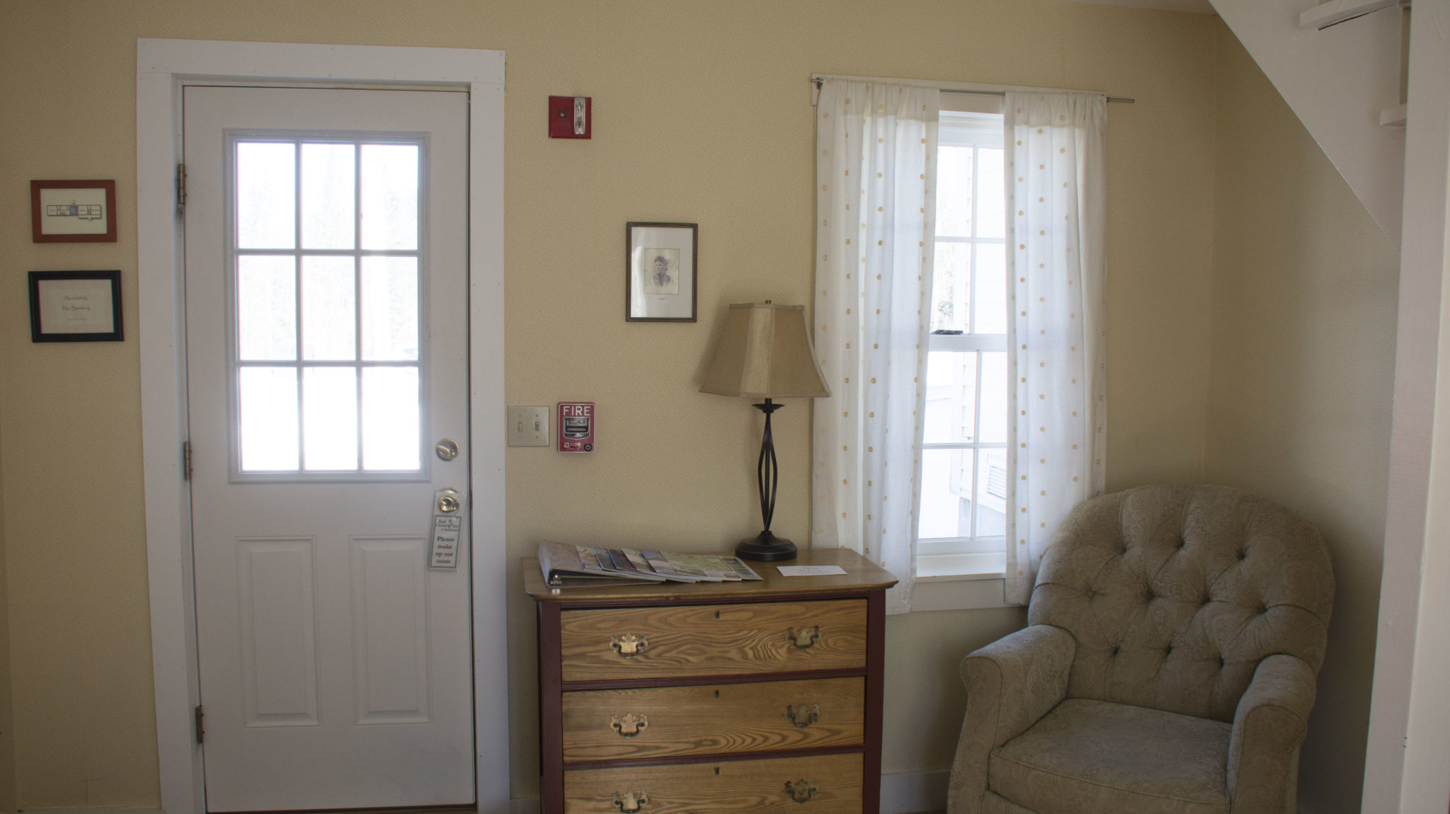 room entrance with dresser and stuffed armchair