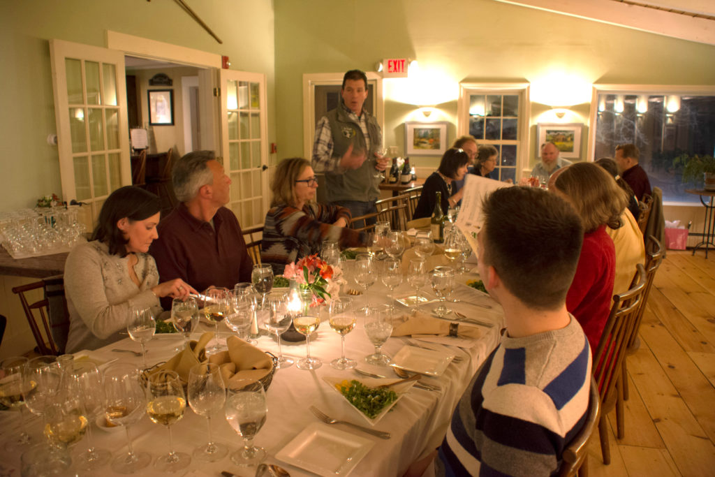 Group of guests dining in the tavern room. Wine glasses and flowers on tables. Man standing above table explaining the different wines.