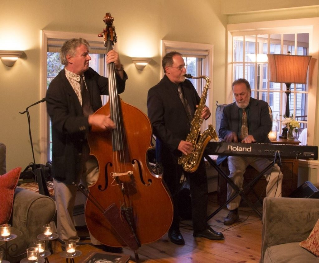 Three jazz musicians playing in the inn dining room.