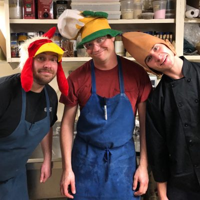 three Red Clover kitchen staff wearing funny hats in the kitchen