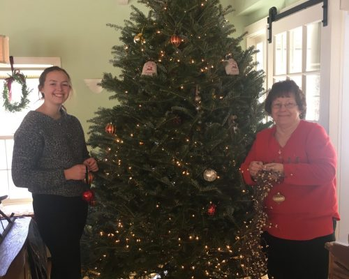 Two innkeepers decorating a Christmas tree in the tavern room