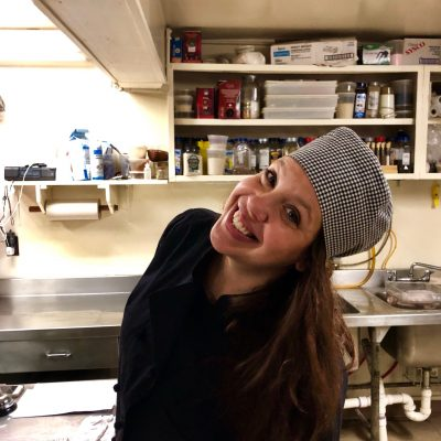 Innkeeper wearing a chef's hat in the kitchen
