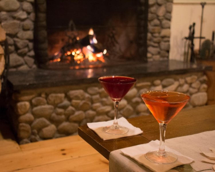 Two cocktails in martini glasses in front of fireplace