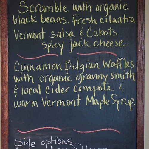 "Chalkboard breakfast menu with colorful writing. Text reads ""Breakfast: Scramble with organic black beans, fresh cilantro, Vermont salsa & Cabots spicy jack cheese. Cinnamon Belgian waffles with organic granny smith & local cider compote & warm Vermont maple syrup. Side options: applewood smoked bacon, sausage, granola, maple yogurt, or 7 grain toast"