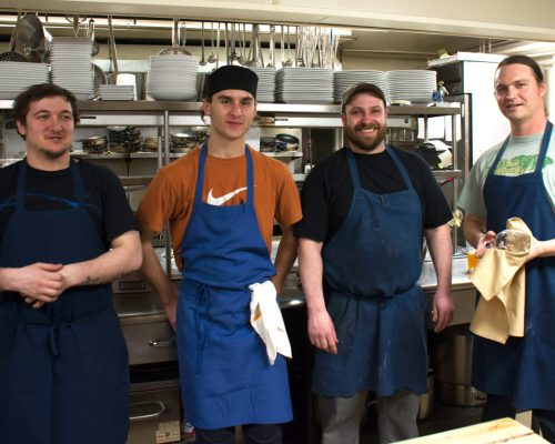 Four chefs in the Red Clover kitchen wearing aprons